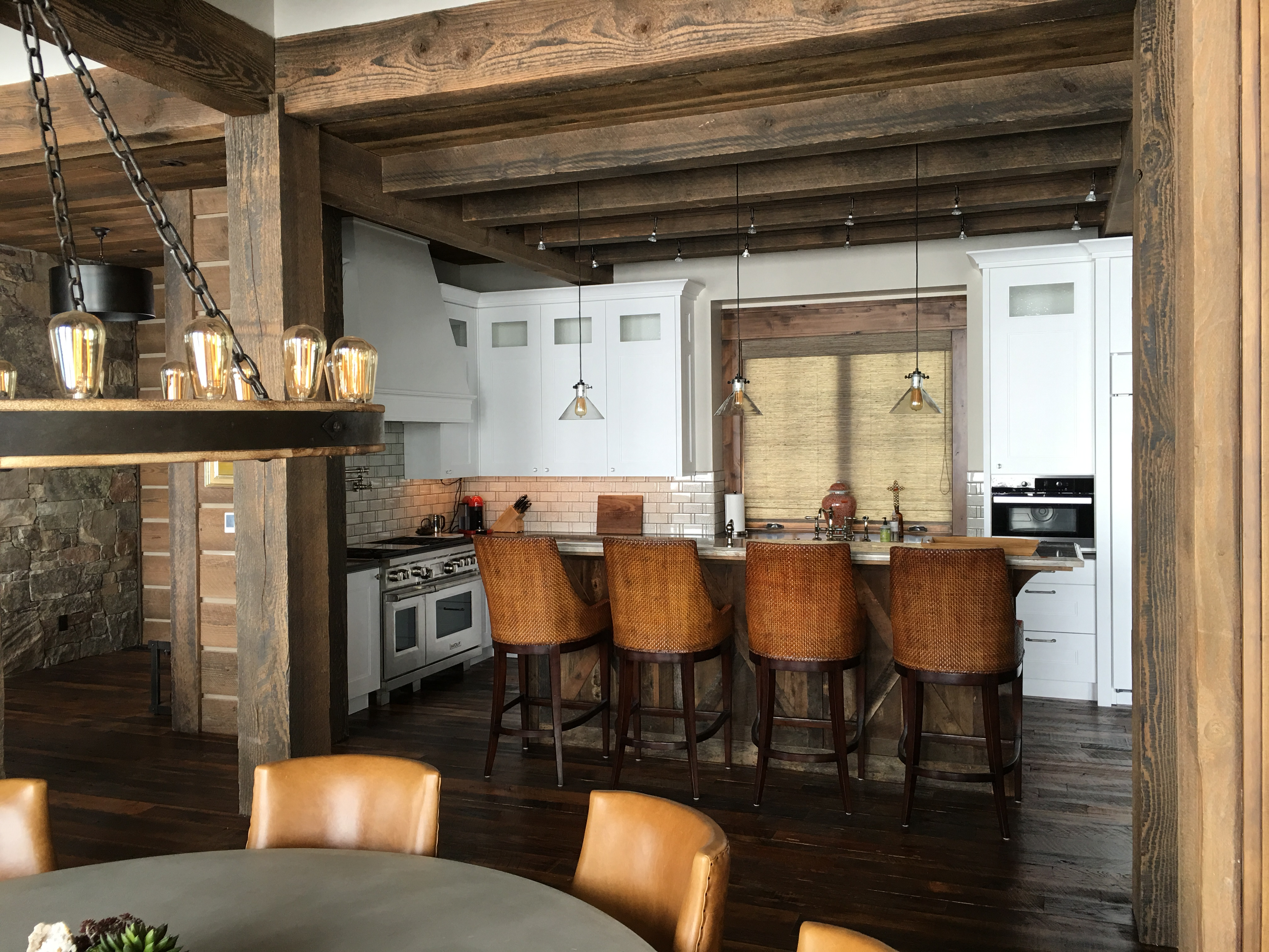 The Reclaimed Lumber Island Helps To Balance White Painted Kitchen In This Rustic Mountain Home